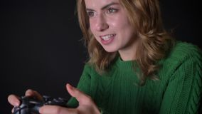 Closeup of adult caucasian woman playing video games on the xbox with excitement and passion indoors.  stock video