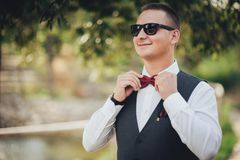Closeup of adult handsome smiling groom in white shirt adjusting. Closeup of adult handsome man adjusting stylish brown male bow tie Stock Images
