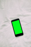 Closeup aerial view of white smart phone with green isolated screen on white wooden surface Stock Images