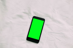 Closeup aerial view of white smart phone with green  screen on white wooden surface Royalty Free Stock Images