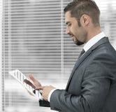 closeup affärsman med minnestavladatoranseende vid fönstret arkivfoton