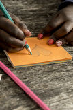 Closeup of African-American girl drawing and coloring a heart sh Stock Photography