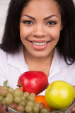 Closeup African AMerican woman with green apple. Beautiful african woman looking into camera and smiling Stock Image