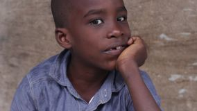 Closeup of African boy`s face. Close up of smiling little african boy face sitting stock video