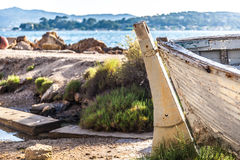 Closeup of aged and abandoned fishing boats laying close to a ri Royalty Free Stock Photos