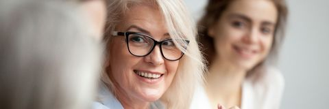 Closeup aged attractive smiling businesswoman listening colleague during briefing meeting. Horizontal close up photo focus aged attractive businesswoman boss in stock photos