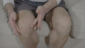 Closeup of aged man leg with osteoarthritis doing self relaxation massage reducing stiffness of knee - stock video