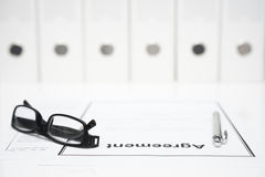 Closeup of agreement, glasses and pen with binders in blurred ba Royalty Free Stock Images