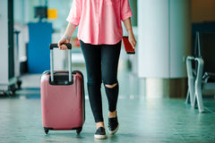 Closeup airplane passenger with passports and boarding pass and pink baggage in an airport lounge. Young woman in Stock Image