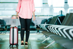 Closeup airplane passenger with passports and boarding pass and pink baggage in an airport lounge. Young woman in Royalty Free Stock Image