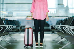 Closeup airplane passenger and pink baggage in an airport lounge waiting for flight aircraft. Young woman in Stock Photos