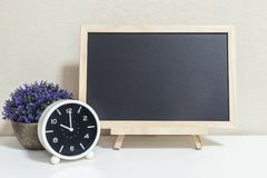 Closeup alarm clock for decorate show 10 o`clock with wood black board on white wood desk and cream wallpaper textured background Stock Images