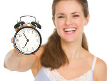Closeup on alarm clock in hand of happy woman Stock Images