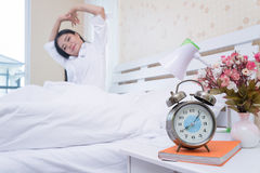 Closeup alarm clock has a nice day with a happy woman in bed after waking up after waking up. Stock Photos