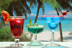 Alcoholic cocktails with fruit on the beach. Closeup alcoholic cocktails rum and vodca with fruit lime strawberry and curacao on the beach royalty free stock image
