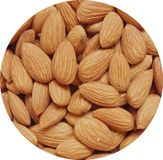 Closeup of Almond nuts heap abstract food product background held in circular window isolated against white background Stock Photography