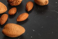 Closeup of almonds, both peeled and whole, on dark board. Space for text on right side.  stock image