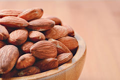 Closeup almonds in wooden bowl. On table Royalty Free Stock Photos