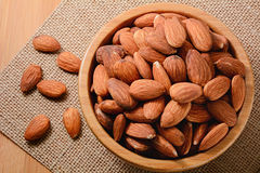 Closeup almonds in wooden bowl. On table Royalty Free Stock Photography