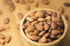 Closeup almonds in wooden bowl. On table Stock Photos