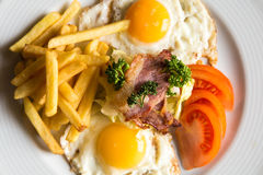 Closeup american breakfast with fried potato. Bacon eggs and tomato Royalty Free Stock Photography