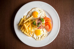 Closeup american breakfast with fried potato bacon eggs and tomato. On wooden background Royalty Free Stock Photo