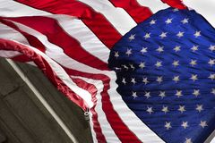 Close up of American Flag Blowing in the Wind with bold red. white and blue colors in Front of Granite Building Royalty Free Stock Image