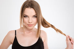 Closeup of amusing beautiful girl playing with hair. Closeup of amusing beautiful sensual tender girl playing with hair on white background stock images
