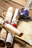 Closeup of ancient scrolls writing by feather with blue ink Royalty Free Stock Images