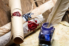 Closeup of ancient scrolls writing by feather with blue ink. On old wooden table royalty free stock images