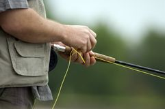 Closeup of angler. Fly fishing with rod, green nature background Royalty Free Stock Photo