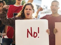 Closeup of angry teen girl protesting demonstration holding posters antiwar justice peace concept Stock Photography