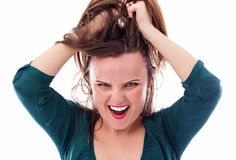 Closeup of an angry young woman pulling her hair Royalty Free Stock Images