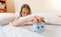 Closeup of annoyed girl reaching for alarm clock. Closeup photo of annoyed girl reaching for alarm clock Royalty Free Stock Photography