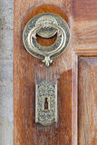 Closeup of antique copper ornate door knocker over an aged wooden door. Fatih Mosque, Istanbul, Turkey stock image