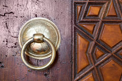 Closeup of antique copper ornate door knocker over an aged wooden door. Suleymaniye Mosque, Istanbul, Turkey royalty free stock image