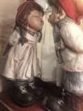 Boy and girl figurines. Closeup of antique figurines of young boy and girl both in period costume kissing Stock Photo