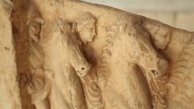 Closeup of antique relief, figures of men riding horses carved on marble plate. Stock footage stock footage