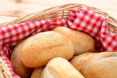 Closeup of appetising crusty petit pain in a basket. Lined with red gingham royalty free stock photography