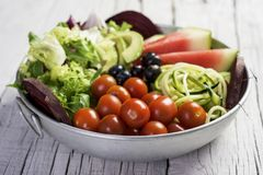 Buddha bowl on a white wooden table. Closeup of an appetizing buddha bowl, made with avocado, cornsalad, lettuce, zucchini, blueberries, watermelon, beet and royalty free stock photography