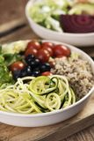 Buddha bowl on a wooden table. Closeup of an appetizing buddha bowl, made with lettuce, cornsalad, quinoa, zucchini spaghetti, blueberries and cherry tomatoes on royalty free stock photography