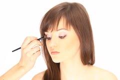 closeup applicerar skugga för konstnärögonmakeup härlig framsidakvinna Fotografering för Bildbyråer