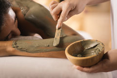 Closeup of applying mud mask. Closeup of applying mud mask with hands of professional therapist Royalty Free Stock Images