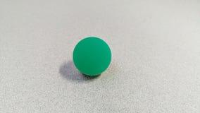 Aqua Opaque Bouncy Ball on Table. A closeup of an aqua opaque luminescent bouncy ball on a table royalty free stock photos