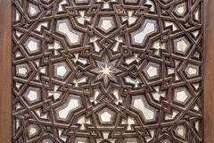 Arabesque ornaments of an old aged decorated wooden door. Closeup of arabesque ornaments of an old aged decorated wooden door Stock Image