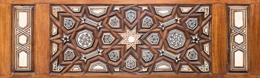 Closeup of arabesque ornaments of an old aged decorated wooden door Royalty Free Stock Image