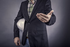 Closeup of an  architect man holding white hardhat under his arm Royalty Free Stock Image