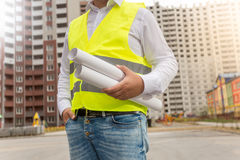Closeup of architect in safety vest posing with blueprints at ne stock image
