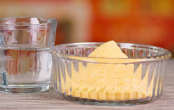 Closeup of an arepas flour inside of a cristal bowl, glas of water on wooden blcakground