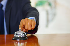 Closeup arm of man wearing blue suit pressing desk bell at hotel reception Royalty Free Stock Photo